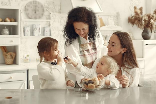 Leute in einer küche. großmutter mit kleinen enkelkindern. kinder essen kekse.