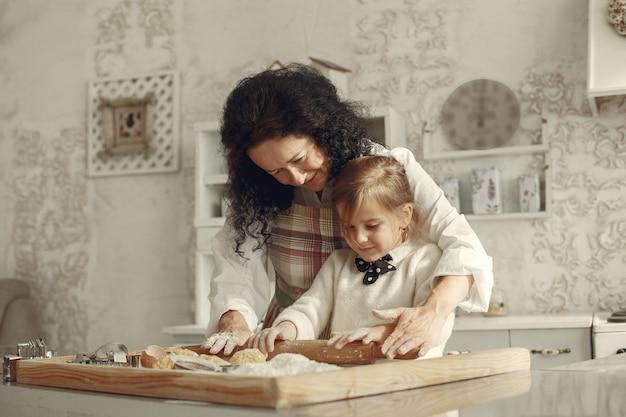 Leute in einer küche. großmutter mit kleiner tochter. erwachsene frau lehren kleines mädchen zu kochen.