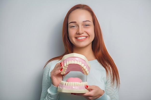 Leute-, medizin-, stomatologie- und gesundheitswesenkonzept - glücklicher junger weiblicher patient mit den großen kiefern.