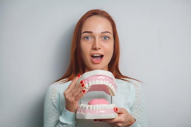 Leute-, medizin-, stomatologie- und gesundheitswesenkonzept - glücklicher junger weiblicher patient mit großen kiefern.