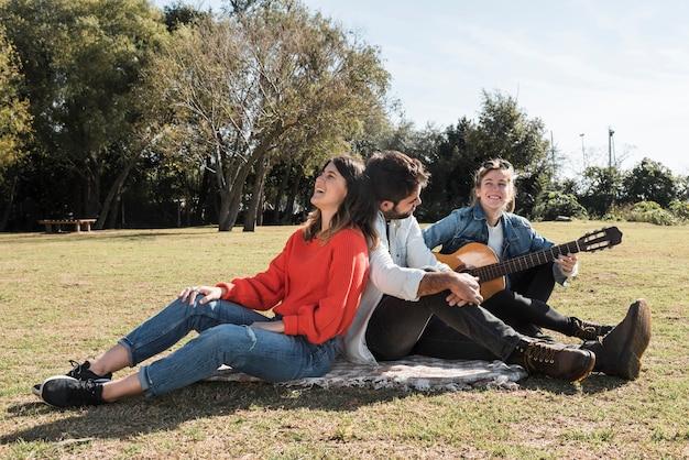 Leute mit gitarre auf bettdecke
