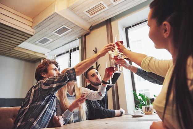 Leute mit gläsern whiskey oder wein feiern und rösten