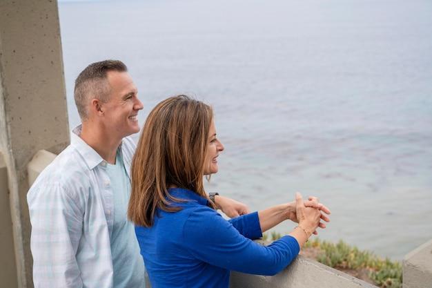 Leute mit mittlerer aufnahme, die aufs meer schauen