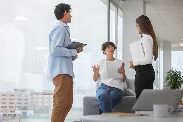 Leute mit mittlerer aufnahme diskutieren bei der arbeit