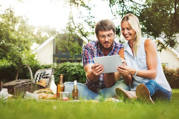 Leute-picknick-zusammengehörigkeits-entspannung-digital-tablet-technologie-konzept