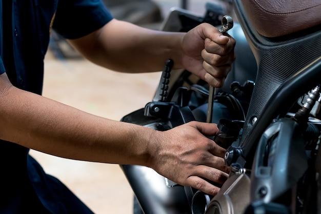 Leute reparieren ein motorrad verwenden sie einen schraubenschlüssel und einen schraubenzieher, um zu arbeiten.