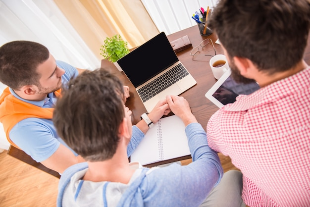 Leute sitzen am schreibtisch und arbeiten.