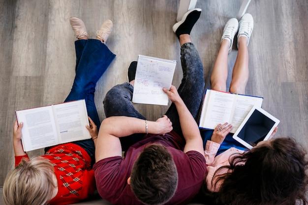 Leute sitzen auf dem boden studieren