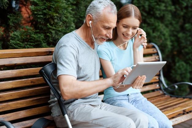 Leute sitzen auf einer bank im park mit tablette