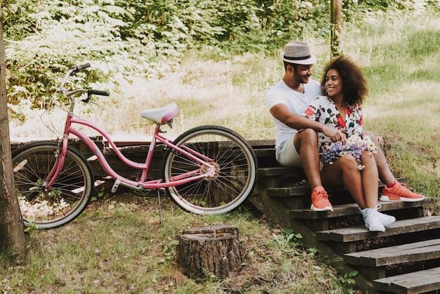 Leute sitzen auf hölzernen treppen im park mit fahrrad