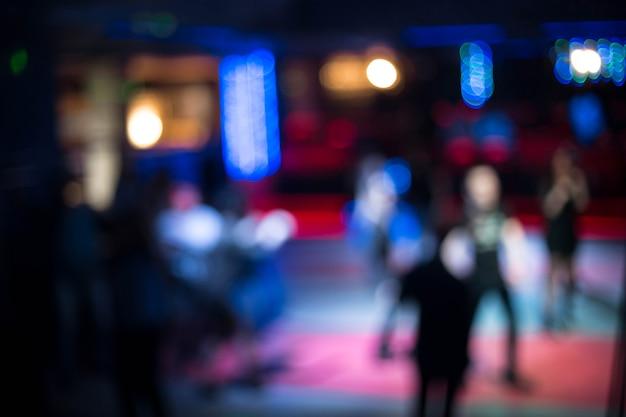 Leute tanzen, die spaß haben und sich in einem unscharfen hintergrund des nachtclubs entspannen. schöne verschwommene lichter auf der tanzfläche