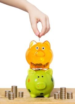 Leute übergeben münze in ein sparschwein.