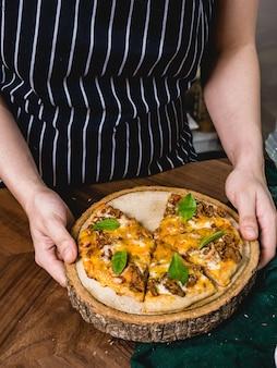 Leute übergeben tragen eine frische gebackene pizza mit fleischkäse und frischem basilikumblatt.