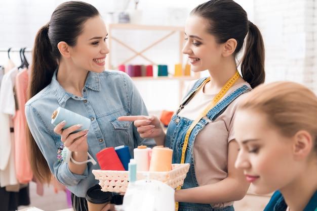 Leute wählen farbe des fadens für neues kleid