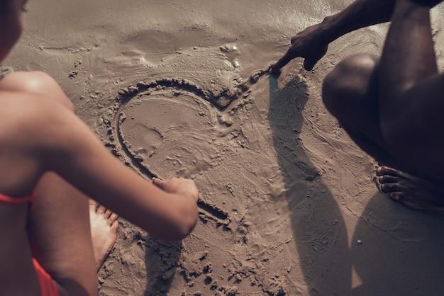 Leute zeichnen bild des herzens auf sand