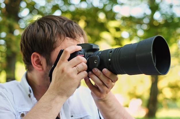 Leutefotografietechnikfreizeit und lebensstilhippie-mann, der digitalkamera mit großer linse hält