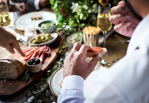 Leutehände, die lebensmittel mit freundbankett essen