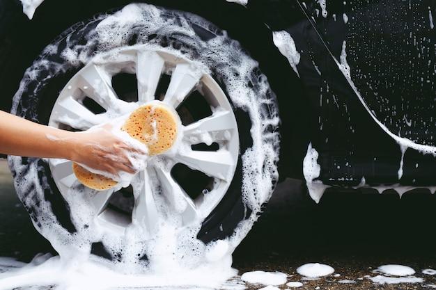Leutemann, der handgelben schwamm zum waschen des autos hält. radreifen reinigen. konzeptautowäsche sauber.