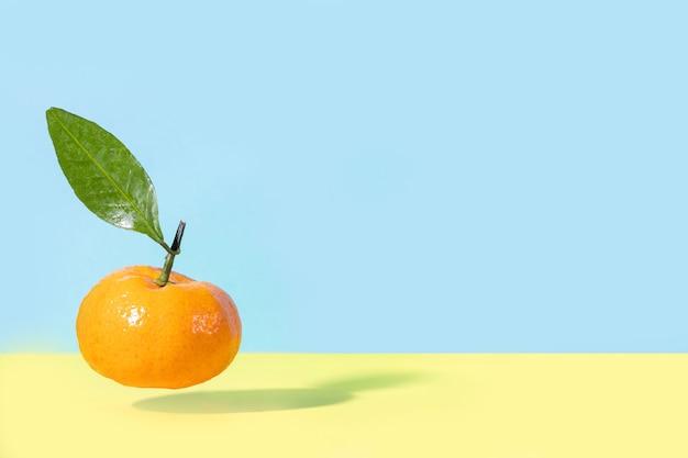 Levitation fliegende lebensmittel mandarine mit grünem blatt auf gelb und blau