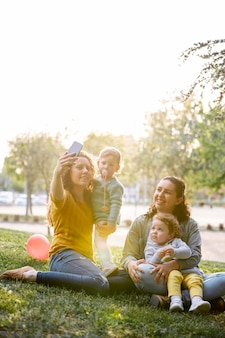 Lgbt familie draußen im park, der ein selfie zusammen nimmt