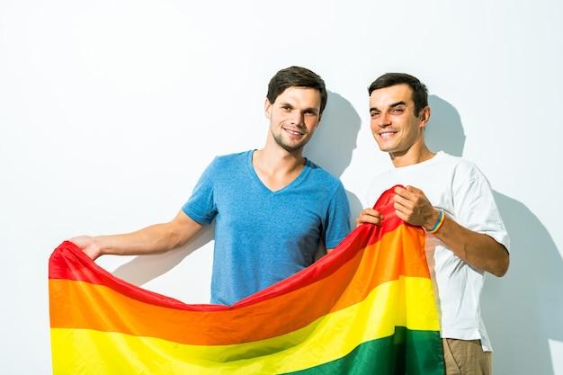 Lgbt-familie, schwules paar, das eine regenbogenfahne hält