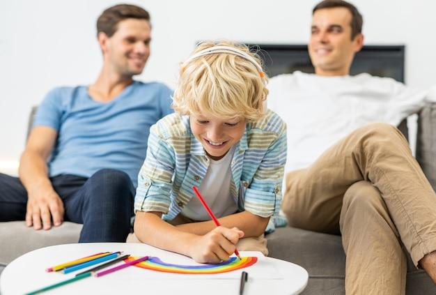 Lgbt-familie, schwules paar mit adoptivsohn - homosexuelle eltern mit ihrem kind haben spaß zu hause