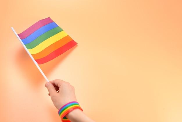 Lgbt-flagge in der frauenhand auf orange