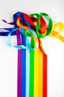 Lgbt-flaggensymbol gemacht von den satinbändern auf einem weißen hintergrund. ein regenbogen von bändern mischt sich miteinander