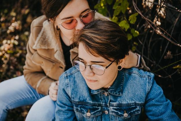 Lgbt-frauen. junges lesbisches paar, das zusammen im park geht. zarte beziehung. selektiver fokus