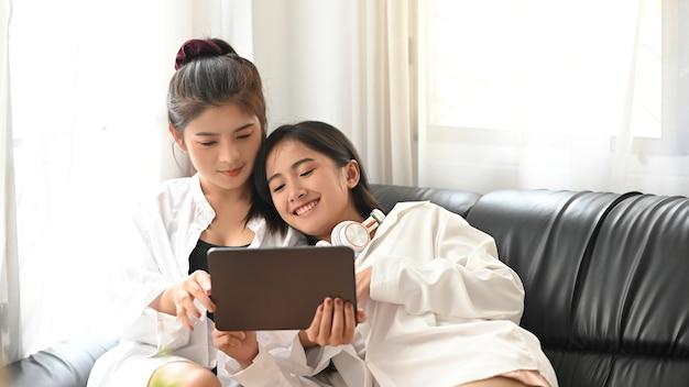 Lgbt, glückliche junge niedliche asiatische homosexuelle frau, die im schlafzimmer zu hause entspannt