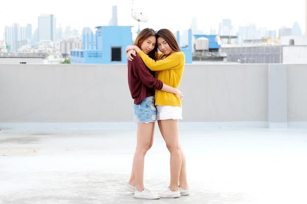 Lgbt, junge nette asiatische lesbische paare, die mit glück auf ihrer datierung huging und lächeln