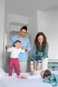 Lgbt mütter zu hause im schlafzimmer mit ihren kindern