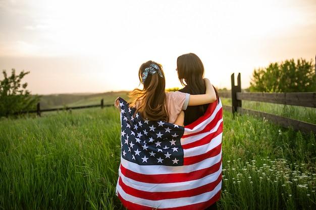 Lgbt-paar umarmt sich kauernd durch usa-flaggenansicht von der hinteren landschaftsansicht im grünen weizenfeld bei sonnenuntergang.