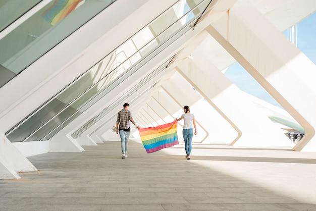 Lgbt-paare, die regenbogenflagge halten