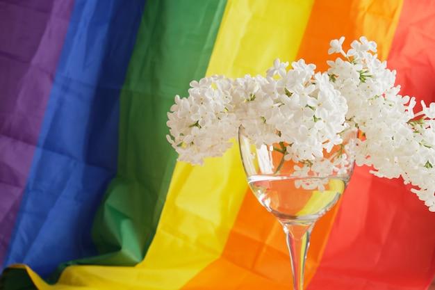 Lgbt-regenbogenband und ein strauß weißer flieder im glas. stolzes bandsymbol. platz kopieren. konzept der lgbt-rechte.
