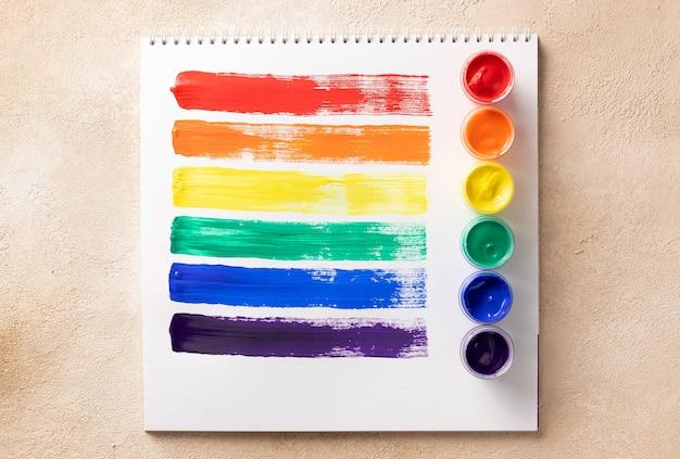 Lgbt-regenbogenfahne in skizzenbuch und farbdosen gemalt