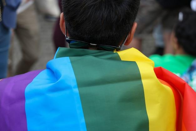 Lgbt-regenbogenflagge bedeckt an zurück von einem mann, der in parade geht.