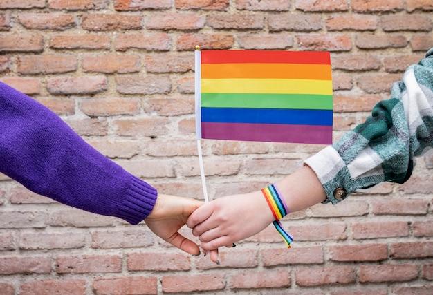 Lgbt-stolzkonzept. homosexueller lebensstil. ein wahres lesbisches paar, das mit dem ikonischen regenbogensymbol umarmt und küsst.