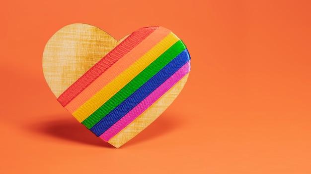 Lgbt-symbol. holzherz mit lgbt-regenbogen auf einem orangefarbenen hintergrund.