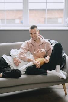Lgbtq-paar, das sich auf der couch entspannt. unterschiedliches familienlebensstilkonzept.