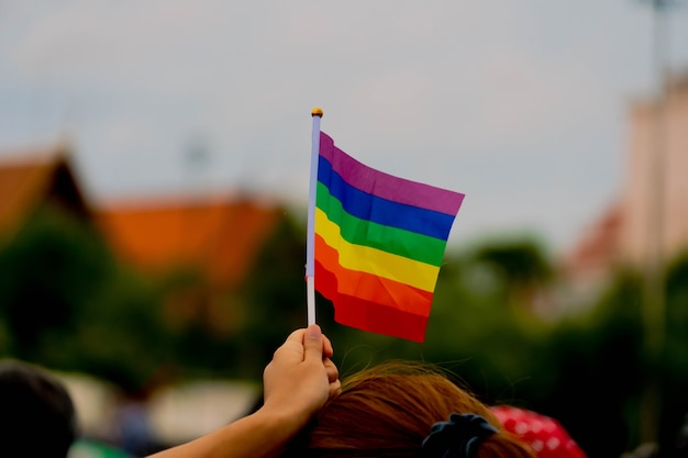 Lgbtq regenbogenfahnen halten in der hand