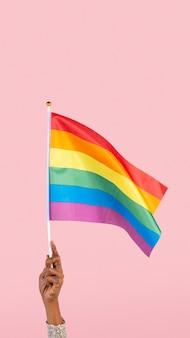 Lgbtq+-stolzflagge mit erhobener hand der frau