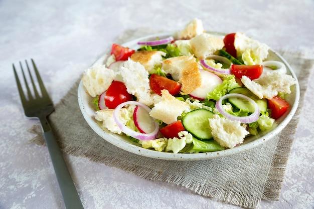 Libanesischer salat fattoush. gesundes vegetarisches essen. traditioneller libanonsalat mit geröstetem fladenbrot und gemüse in der weißen platte auf der leinwand serviette mit gabel. nahansicht.