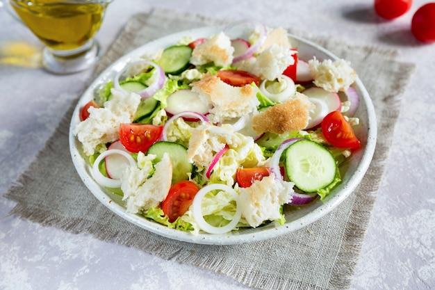 Libanesischer salat fattoush nahaufnahme mit geröstetem fladenbrot und gemüse in der weißen platte auf der leinwand serviette mit olivenöl.