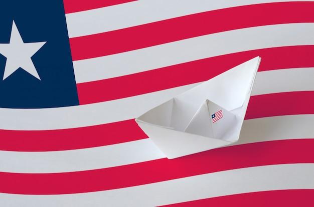Liberia flagge auf papier origami schiff nahaufnahme dargestellt. handgemachtes kunstkonzept
