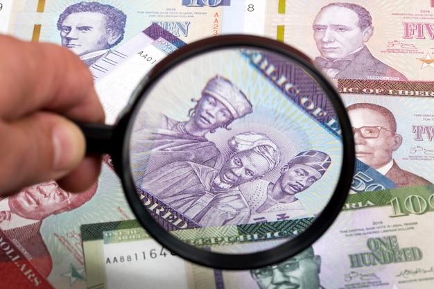 Liberianisches geld in einer lupe ein geschäftshintergrund