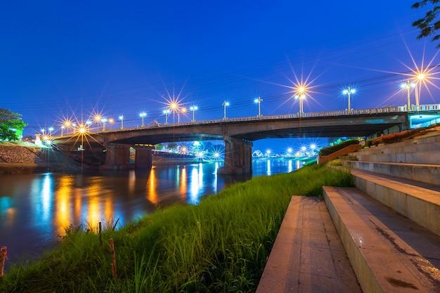Licht auf dem nan river in der nacht auf der brücke (naresuan bridge) in phitsanulok city thailand.