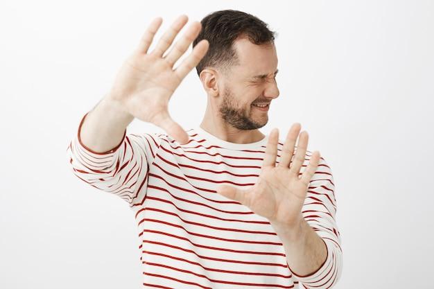 Licht ausschalten. porträt eines unzufriedenen unbequemen männlichen models in lässigem outfit, das die handflächen zu sich zieht und das gesicht dreht, um sich vor glänzendem licht oder schlag zu verstecken