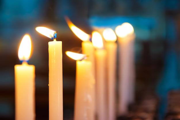 Licht der kerzen in der kirche auf dem schwarzen hintergrund Premium Fotos