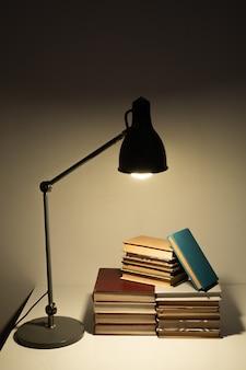 Licht der lampe, die auf stapel von büchern oder handbüchern des zeitgenössischen schul- oder studenten auf schreibtisch in der dunkelheit nachts fällt